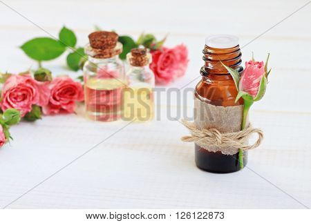 Essential rose oil in bottle, flower tied on label. Aromatic skin-beautifying treatment.