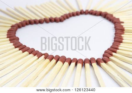 Closeup of match sticks arranged to form a heart shape with depth of field