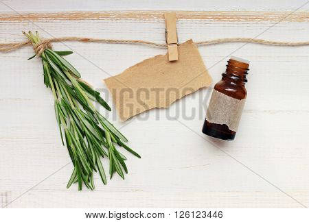 Fresh rosemary twigs and bottle essential oil, empty parchment label.