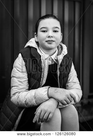 Black and white portrait of a smiling girl on the street