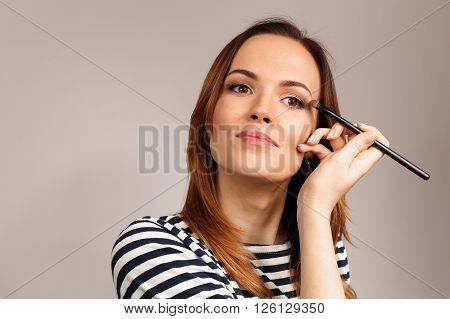 Applying eye makeup products on woman's face. Eyes Makeup. Eyes shadows. Eye shadow brush. Perfect face makeup process.