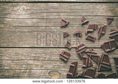 broken dark chocolate on old wooden background