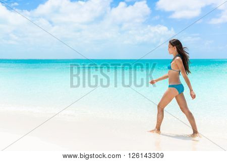 Beautiful bikini woman walking relaxing on sunny perfect white sand beach and pristine turquoise clear water in idyllic tropical destination during summer travel. Luxury getaway vacation.