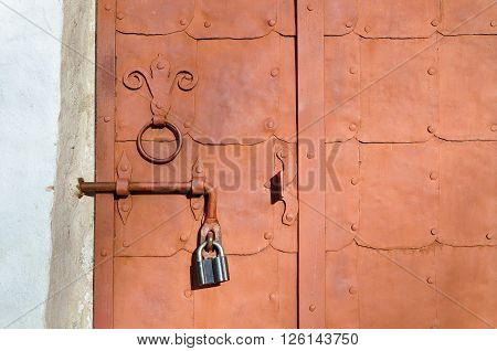 Aged brown metallic door with rivets and aged metal door handle in the form of stylized lily. Grunge background in rusty tones