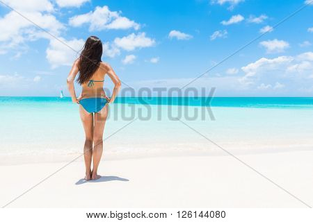 Bikini woman standing on white sand beach vacation getaway. Sexy fashion model with lean legs and toned body relaxing on luxury paradise sun destination on summer vacation. Caribbean holidays.