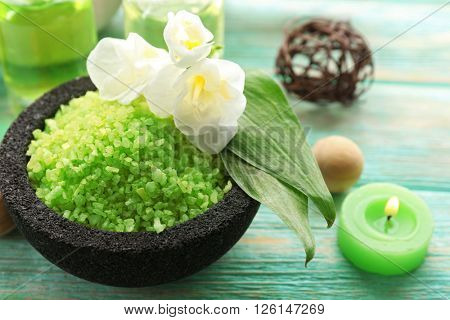 Sea salt crystals in a bowl and exotic flowers, close up