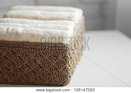 Wicker basket with towels inside on table, closeup
