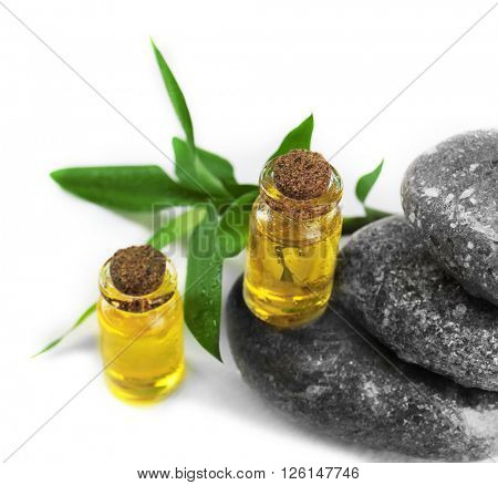 Bottles of tea oil and spa stones, isolated on white