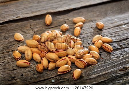 Dried pistachio seeds set on old wooden surface