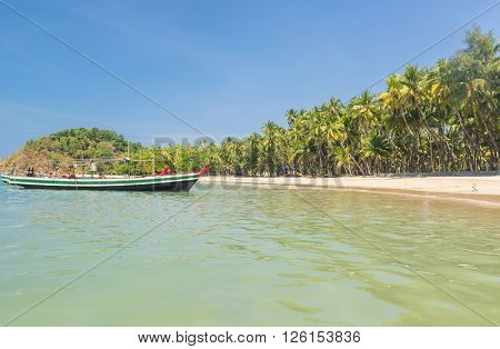 Beautiful beach of Ngapali with fisherman boat and palms hanging over the sea, Myanmar
