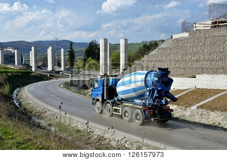 Four axles truck mixer on the road near by highway under construction