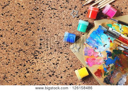 Colorful paints and pencils with palette on cork board background.