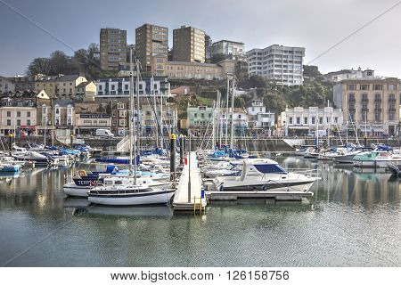 TORQUAY DEVON UK circa APRIL 2015 Yachts moored in Torquay Harbour with various accommodation and homes in the background.