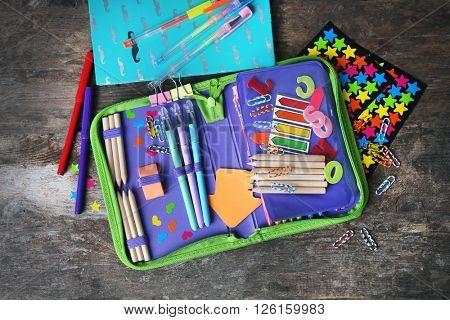 Pencil case with various stationery on old  wooden table
