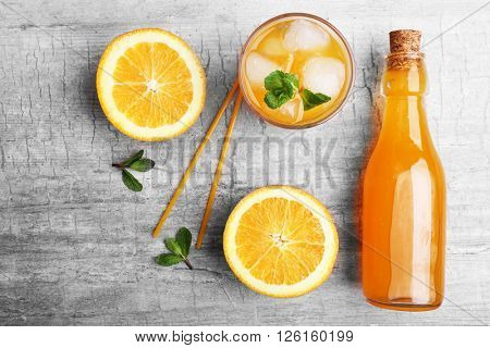 Fresh cocktail preparation: soda bottle, slices of an orange,  mint on grey table background, top view