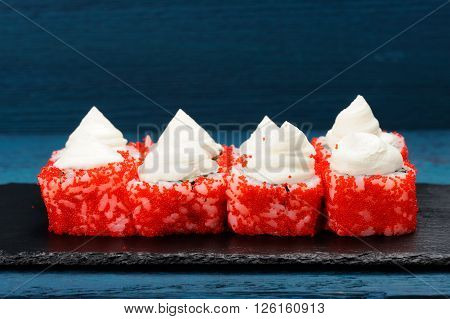 Homemade tasty sushi with red tobiko roe and cream cheese on blue background closeup