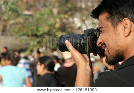HYDERABAD,INDIA-MARCH 10: Indian photographer shoot the crowd on day,open roads program on March 10,2016 in Hyderabad,India.