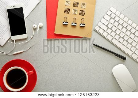 Workplace with mobile phone, peripheral devices and stationery on grey table