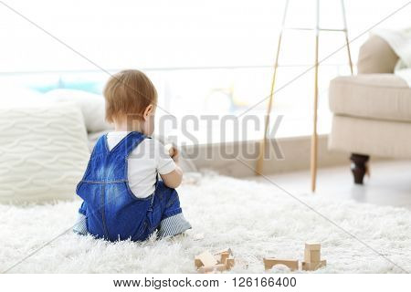 Baby playing with meccano on carpet