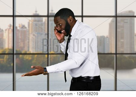 Friendly black guy with cellphone. Manager's phonecall on city background. Businessman establishing contacts. Manners mean a lot.