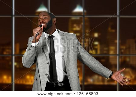 Afro man with microphone singing. Stage performance in night city. Special guest on tv show. Man has true talent.