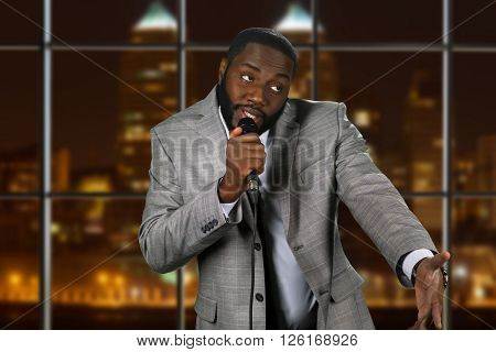 Expressive black man with microphone. Stand-up comedian on night background. Comedy show on local television. Old funny story. poster