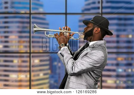Afro trumpeter in black hat. Trumpet performance on skyscraper background. Reggae music for your pleasure. Classy musician on stage.