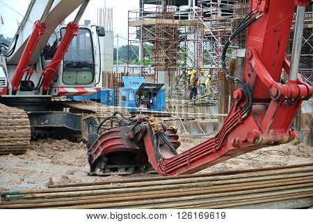 SELANGOR, MALAYSIA -MARCH 25, 2015: Sheet pile cofferdam driven machine at the construction site. The machine drove the sheet pile to the earth using vibrated hydraulic arm. Workers control.