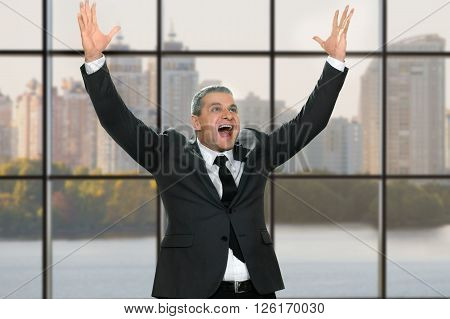 Happy businessman with arms raised. Elated boss on daytime background. Think about the jackpot. Skyrocket the income.