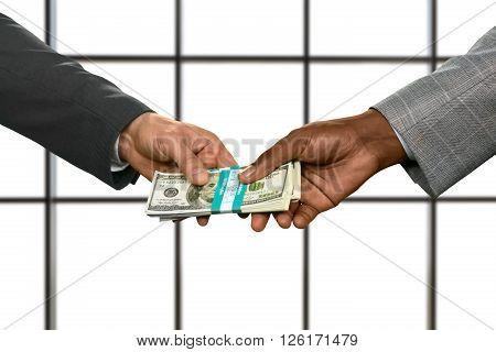 Businessmen's hands passing money bundle. Obtaining dollars on white background. Money rules the world. The path takes strange turns.