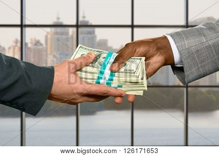 Male hand taking big money. Money transfer on city background. Strong leader's inheritance. Purchasing real estate on credit.