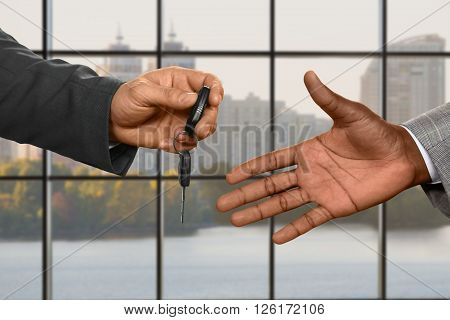 Caucasian businessman's hand giving key. Passing car keys at daytime. What's mine is yours. Say no to public transport.