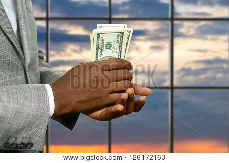 Darkskinned man's hand holding cash. Businessman with dollars at sunrise. Warm up your pocket. Fresh and crispy. ** Note: Visible grain at 100%, best at smaller sizes