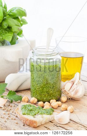 Fresh made basil pesto on bruschetta besides all the ingredients necessary to prepare this particular recipe with hazelnuts in the place of the pine seeds used in the traditional pesto recipe.