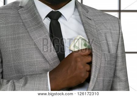 Afro businessman hides money. Rich man on white background. Feed the greed. Master of fraud.