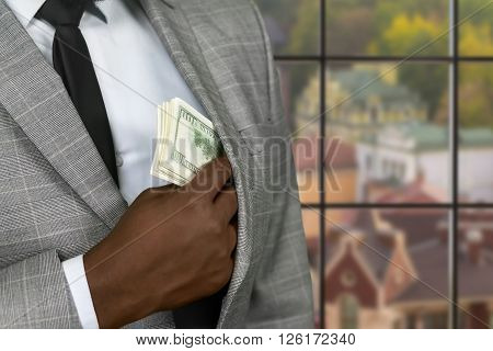 Black businessman hiding cash. Wealthy man on urban background. Criminal is always cautious. Getting away from law.