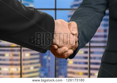 Adult caucasian businessmen shake hands. Handshake in evening megalopolis. It's nice to meet you. Partner for election campaign.