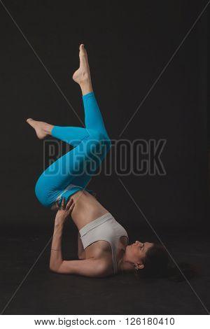 Beautiful sporty yogi girl practices yoga asana over black background