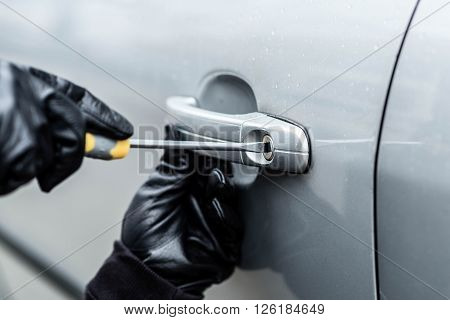 Close up on car thief hands trying to steal a vehicle with screwdriver poster