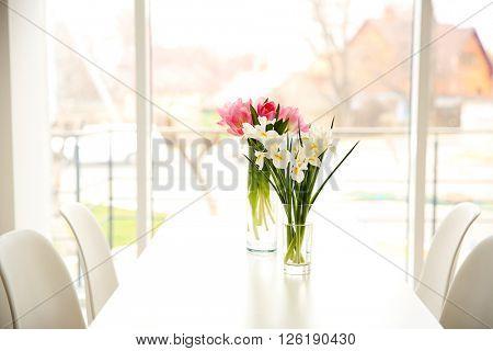 Beautiful tulips and irises on dinning table on window background