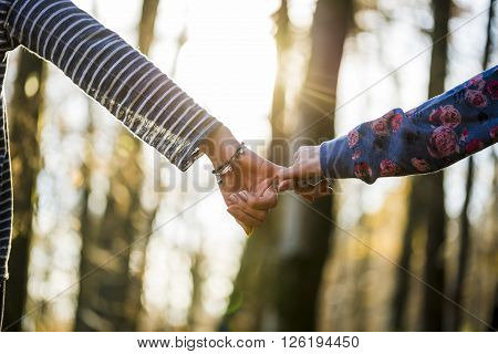 Low angle view of two female friends or partners holding pinkies with background of blurred trees and bright sunshine.