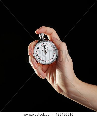 Stopwatch in hand on black background, close up