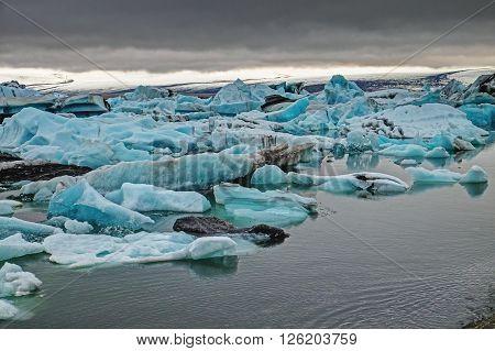 The Jokulsarlon glaciar lagoon in Iceland with dark clouds