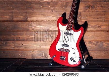 Electric guitar on dark lightened wooden background