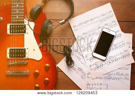 Electric guitar with headphones, mobile phone and notes on wooden background