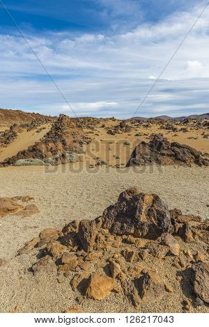 Acute yellow rocks jut out of the sand in a desert valley at the foot of the volcano Teide on Tenerife.