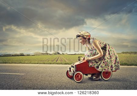 Woman driving a toy car