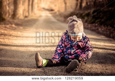 Little baby toddler sitting and playing on dirt road in winter evening