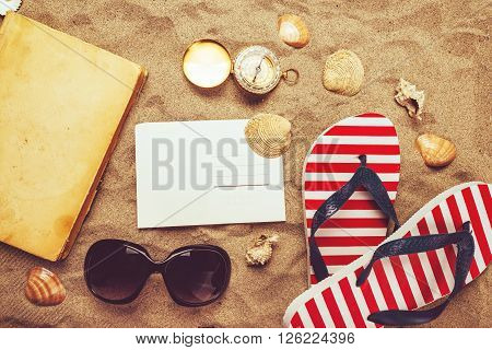 Beach ready summer holiday vacation accessories on sandy beach - vacation mood and summer lifestyle objects in flat lay top view arrangement.