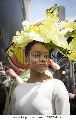 NEW YORK - MAR 27 2016: A woman wearing an Easter bonnet of yellow flowers and butterflies walks along 5th Ave on Easter Sunday for the traditional Easter Bonnet Parade in Manhattan on March 27, 2016.